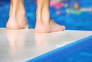 Pair of feet at edge of diving board, waiting for pool to clear